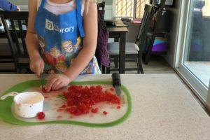 child chopping cherries