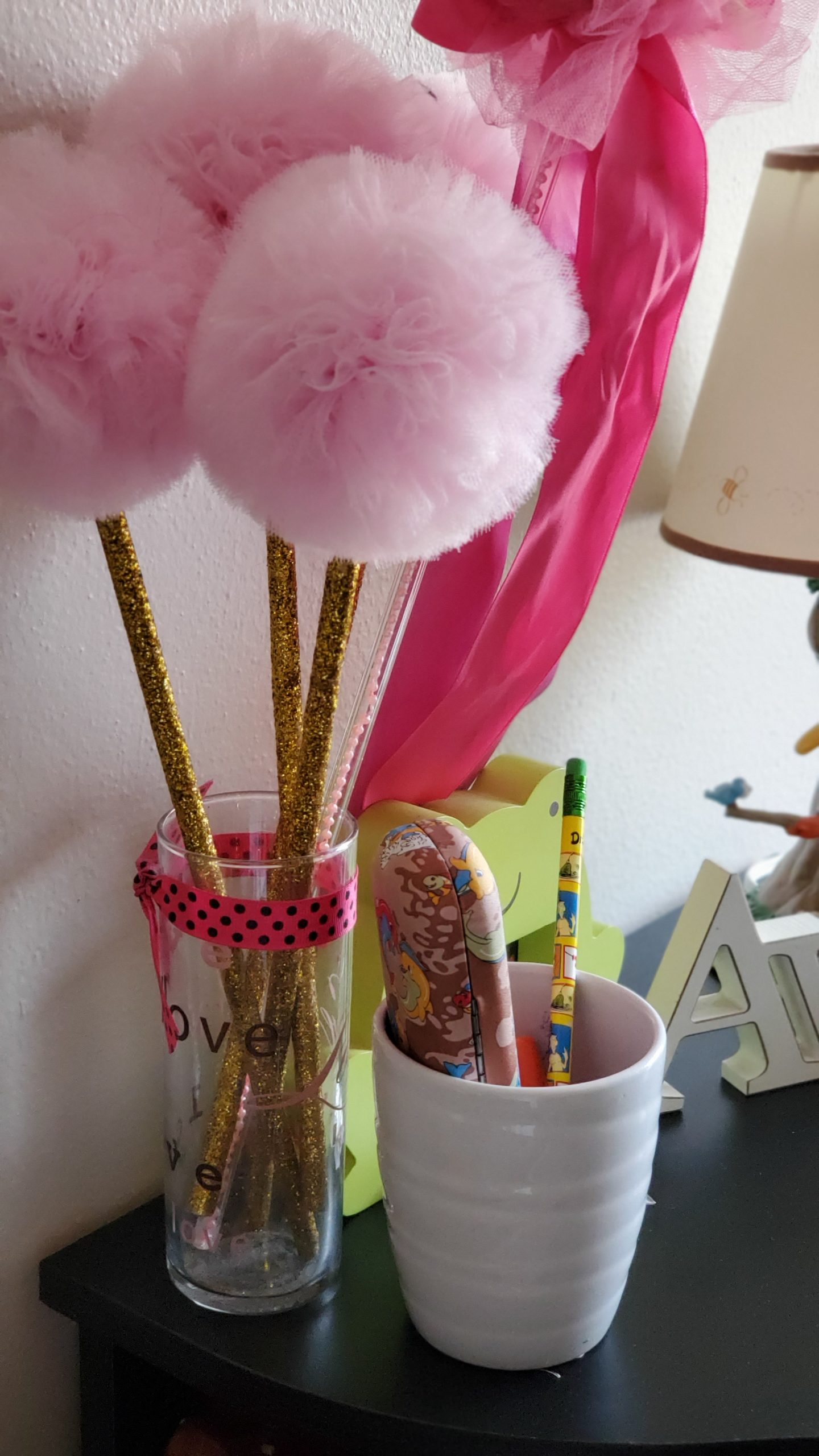 Personal touches on a desk space: handmade wands and a vase for pencils