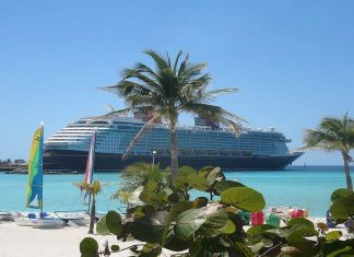 View from a beach of cruise ship docked in tropical port