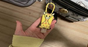 Giraffe hand sanitizer holder attached to a backpack