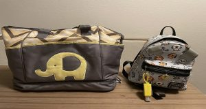 Yellow and gray diaper bag sitting next to a small gray backpack