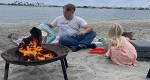 A man and child play in the sand near a bonfire