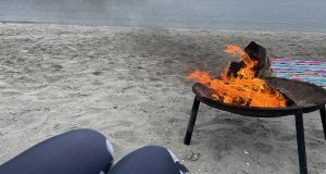 A lit bonfire set up with a beach in the background
