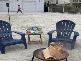 Two chairs and a table with smores ingredients are set up near a bonfire